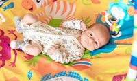Baby boy in a rocking cradle at home