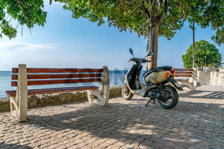 A scooter next to a bench and a tree with the see in the background. Travel and adventure concept. A scooter travel and adventure concept. A scooter in Nessebar, Bulgaria