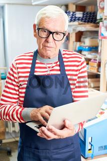 Senior craftsman browsing modern laptop