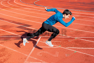 Runner starting his sprint on running track in a stadium.