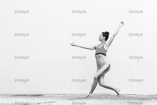 Fit sporty active girl in fashion sportswear doing yoga fitness exercise in front of gray wall, outdoor sports, urban style. Black and white photo.