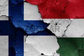 flags of Finland and Hungary painted on cracked wall