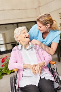 Glückliche Seniorin im Rollstuhl mit Pflegekraft