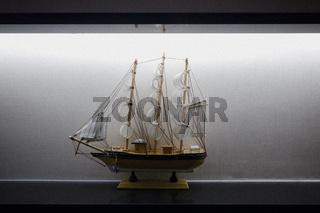 Model Sailboat Frigate Sitting on Display Shelf Lights Black White Elegant Decoration Centered