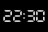 Real white led digital clock on a black background showing time 22:30