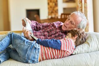 Opa beim Vorlesen aus einem Buch mit seinem Enkel