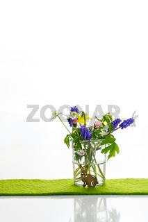 Kleine Blüten in einer Vase mit einem kleinen Hase.  Ostern. Dezent.