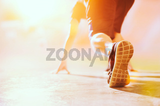 Athlete in running start pose on the street with copy space