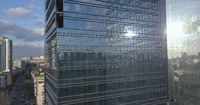 Glass office building and view of the modern city with passing cars and railway. 4K video, 240fps, 2160p.