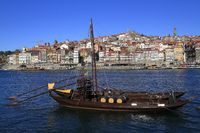 Traditional rabelo boats, Porto city skyline, Douro river and and Dom Luis or Luiz iron bridge. Porto