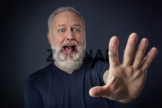 Panicked elderly man with his stretched hand forward