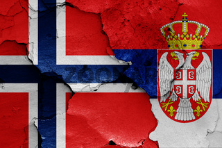 flags of Norway and Serbia painted on cracked wall
