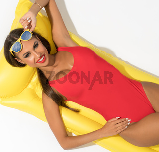 Sexy girl on swimming mattress in studio