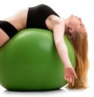 Female gymnast lying on back on green big fitball