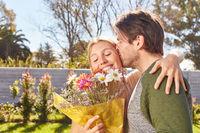 Mann küsst Freundin und schenkt ihr Blumenstrauß