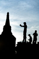 Silhouetted young male tourists photograph pagoda temples at Bagan, Myanmar.
