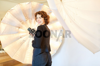 Lächelnde Fotografin mit Kamera vor Studioleuchte