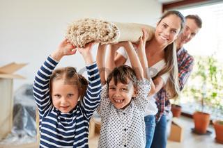 Kinder und Eltern tragen einen Teppich