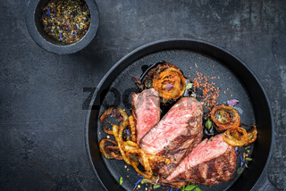 Modern Style classic dry aged sliced roast beef with fried onion rings served as top view in a minimalistic design cast-iron skillet