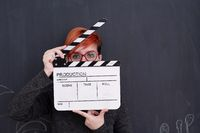 redhead woman holding clapper on black background
