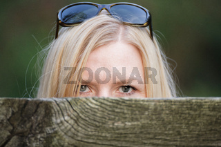 Stalking woman behind a fence hiding her face.