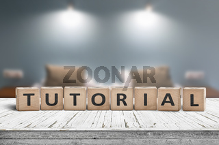 Tutorial sign on a wooden table in a room with lights