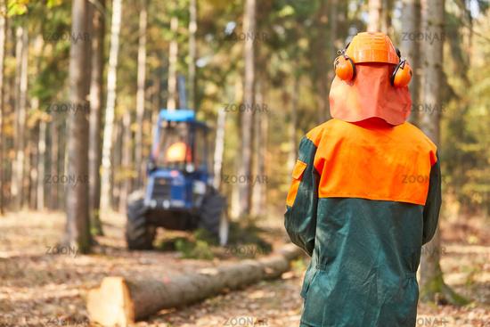 Waldarbeiter in Schutzkleidung beobachtet Forwarder