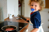 Child at the stove in the kitchen