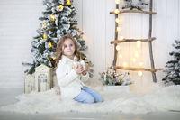 Little girl unpacking christmas gift at Christmas decoration