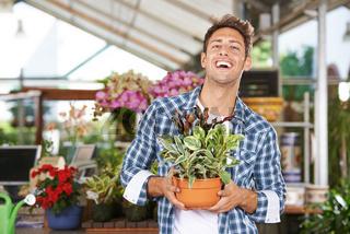 Mann mit Pflanze im Gartencenter