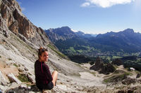attractive female hiker sitting on a rock and enjoying a great view of the Dolomites above Cortina d