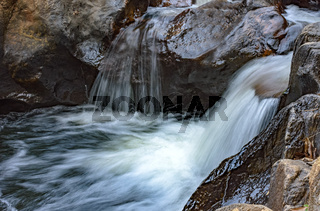 Small river with clear waters and cascade running through the rocks