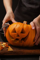 Hands cutting, carving pumpkin into jack-o-lanterns for halloween