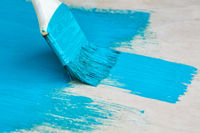 brush with turquoise paint close-up on a painted surface background