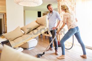 Junges Paar beim Staubsaugen im Wohnzimmer