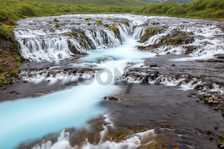 Bright powerful Bruarfoss waterfall in Iceland with cyan water.