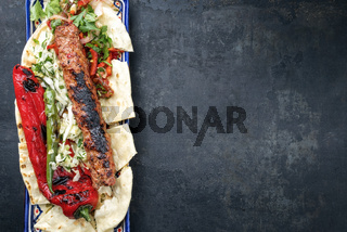 Traditional Adana Kebap with tomato and salad on a flatbread with copy space right