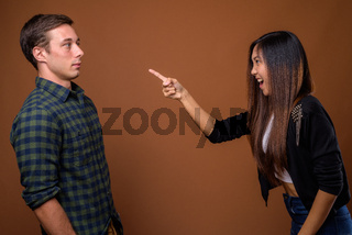 Studio shot of young multi-ethnic couple together against brown
