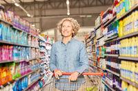 Seniorin mit Einkaufswagen im Discounter