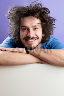 handsome young man displaying a banner ad isolated on color background, copy space on white board