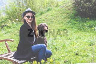 Frühling: elegante junge Frau mit Hut und Hund 20 - 30 Jahre, genießt den Sonnenschein im Garten.