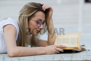 Portrait of young woman reading a book lying on the bench in the park