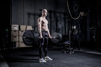 Muscular Man Doing Heavy Deadlift Exercise. Dramatic color grading.