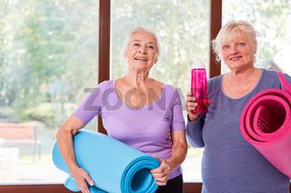 Zwei vitale Senior Frauen mit Yogamatte