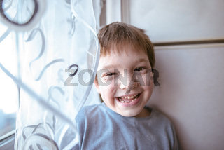 Portrait of playful laughting little boy at the window