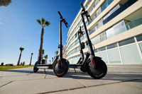 Three black colour electric scooters for adults outdoors on blue sky tropical climate landscape background, no people. Modern technology land vehicle eco alternative transport concept