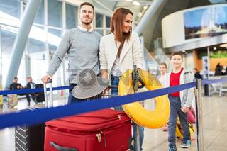 Familie mit Kindern und Gepäck im Flughafen