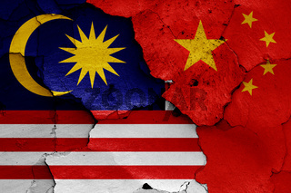 flags of Malaysia and China painted on cracked wall