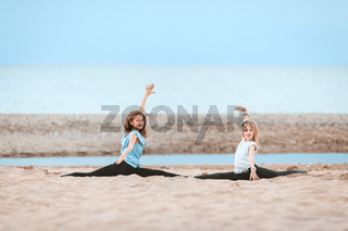 Two young girls doing splits, gymnastics on the beach
