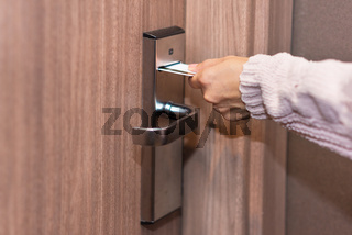 Woman hand inserting card to open electronic lock in hotel door